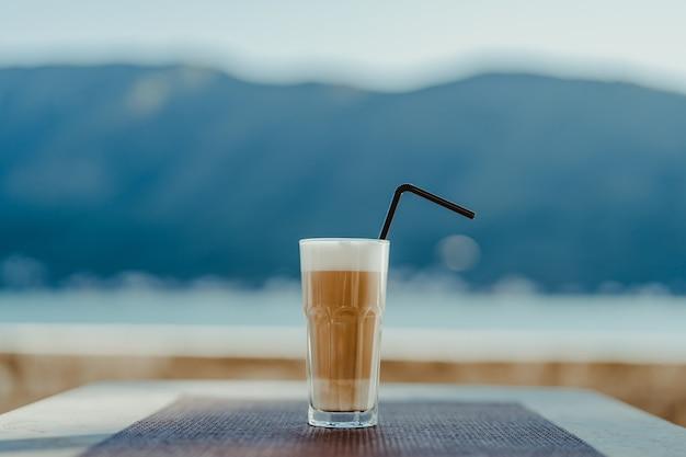 Vetro sfaccettato con caffè latte e paglia.