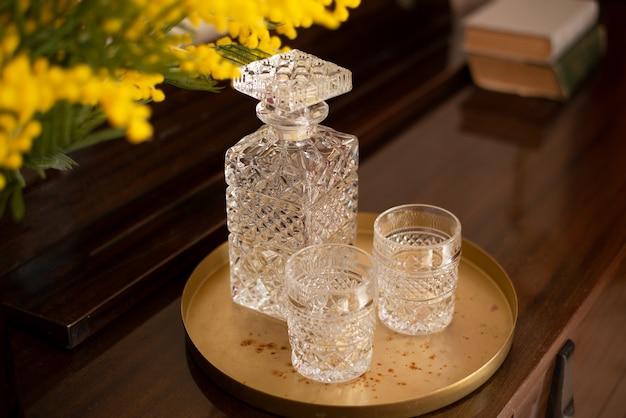 Bicchieri sfaccettati e una bottiglia su un vassoio in stile sovietico su uno sfondo di fiori retrò di
