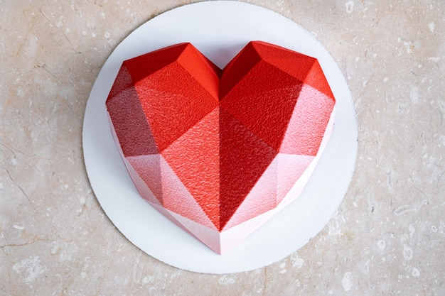 Torta di mousse di cuore rosso sfaccettato con rivestimento in velluto su un tavolo di marmo rosa tenue.