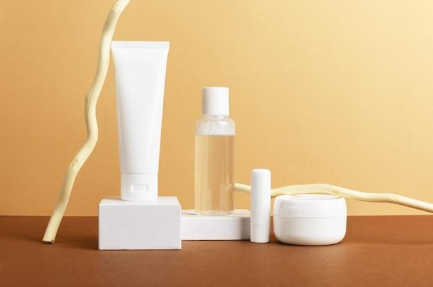 Composizione di bottiglie di cosmetici per la cura del viso e del corpo su sfondo marrone.