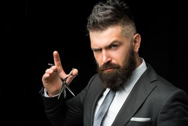 Cura del viso. uomo barbuto in tailleur formale. brutale hipster maschio tagliare i capelli con le forbici da parrucchiere. uomo d'affari fiducioso al barbiere.
