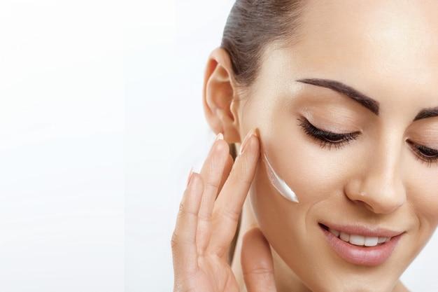 Cura del viso femminile che applica crema e sorridente ritratto di donna con crema cosmetica sulla pelle