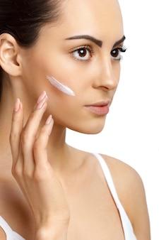 Cura del viso femminile che applica crema