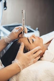 Procedure di pulizia del viso eseguite in un salone spa per una donna bruna sdraiata sul divano durante la sessione di trattamento