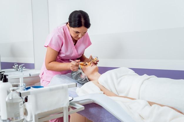Procedura cosmetica facciale nel salone spa. la procedura per applicare una maschera sul viso di una bella donna