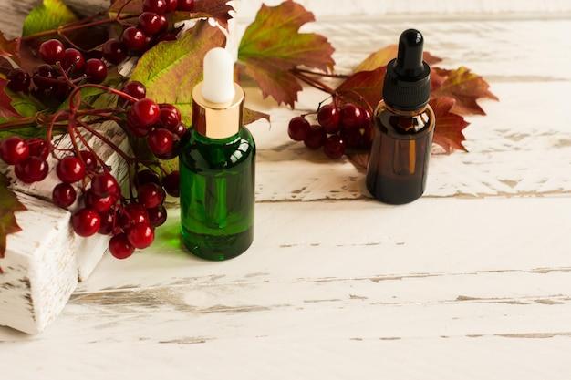 Siero viso in bottiglie di vetro con pipetta, foglie di viburno e bacche su fondo di legno bianco.