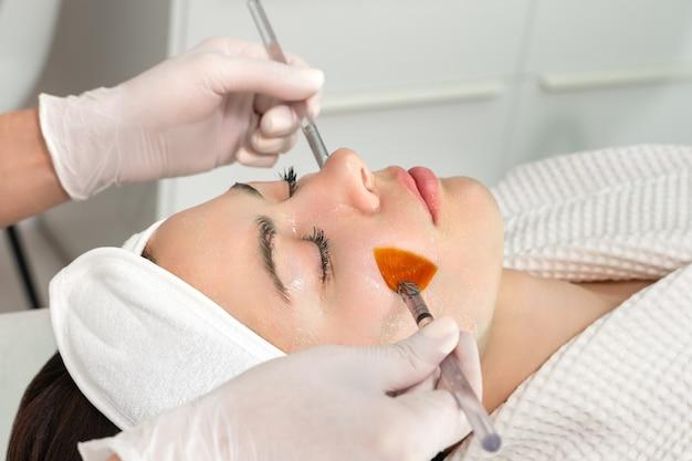 Cura della pelle del viso. una maschera viene applicata al viso di una donna in una clinica di cosmetologia. avvicinamento
