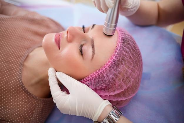 Cura della pelle del viso. la giovane bella donna con ottiene la procedura in un salone di bellezza. cavitazione ultrasonica anti-età, ringiovanimento, procedura di sollevamento. concetto di bellezza