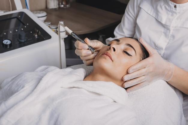 Procedure di lifting della pelle del viso su una signora bruna sdraiata in un salone spa guarita con un nuovo apparato