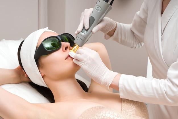 Cura della pelle del viso una maschera viene applicata al viso di una donna in una clinica di cosmetologia da vicino