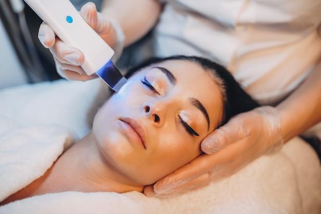 Procedura di trattamento del viso fatto a bruna caucasica con gli occhi chiusi al salone della stazione termale con l'apparato