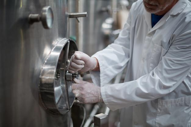 Ingegnere di fabbrica che gira la ruota di controllo del serbatoio