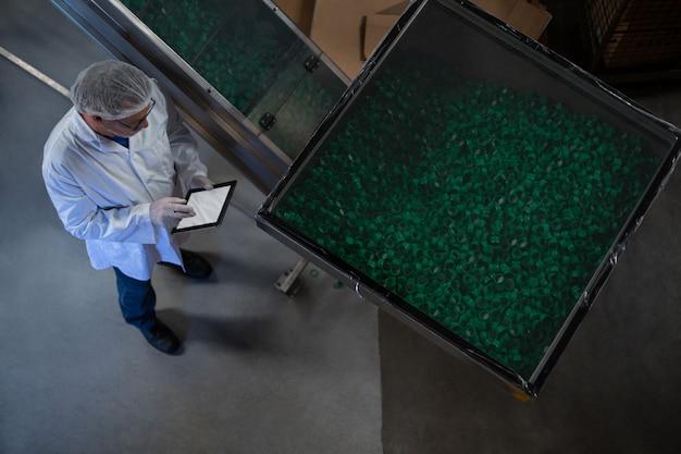Ingegnere di fabbrica che utilizza compressa digitale nella fabbrica