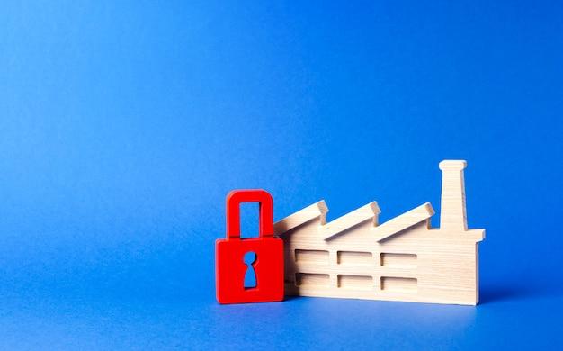 Figurina di fabbrica e chiusura con lucchetto rosso della produzione dannosa congelamento dei beni in bancarotta