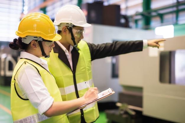 L'ispettore di fabbrica scrive il risultato dell'audit della macchina mentre il manager punta il dito sulla fresatrice cnc