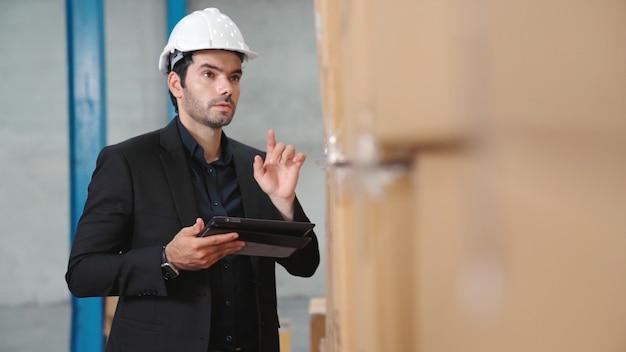 Direttore di fabbrica utilizzando computer tablet in magazzino o in fabbrica. concetto di gestione dell'industria e della catena di fornitura.