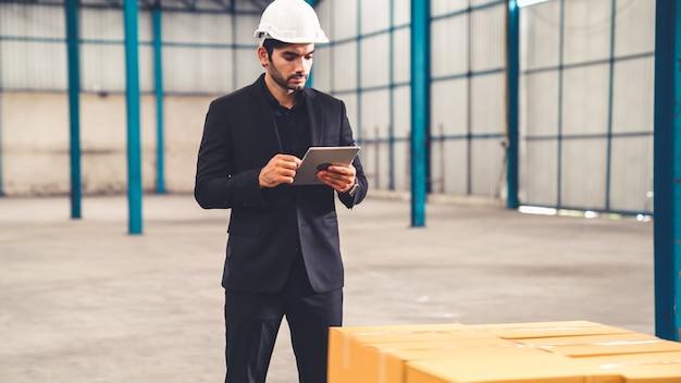 Direttore di fabbrica utilizzando computer tablet in magazzino o in fabbrica