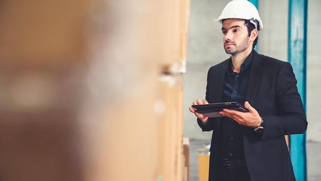Direttore di fabbrica utilizzando computer tablet in magazzino