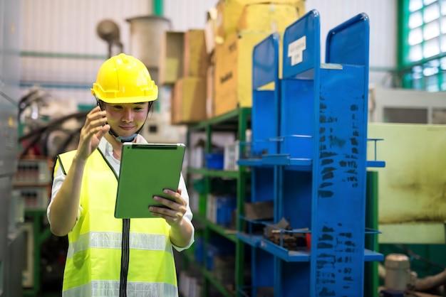 Operaia di magazzino di fabbrica con casco controlla l'inventario delle scorte tramite applicazione aziendale tramite tablet. ha una videoconferenza con un collega del team per chiedere l'attrezzatura mancante.