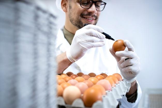 Operaio di fabbrica che controlla la qualità delle uova di gallina nell'azienda agricola e segna un segno ok sul guscio d'uovo.