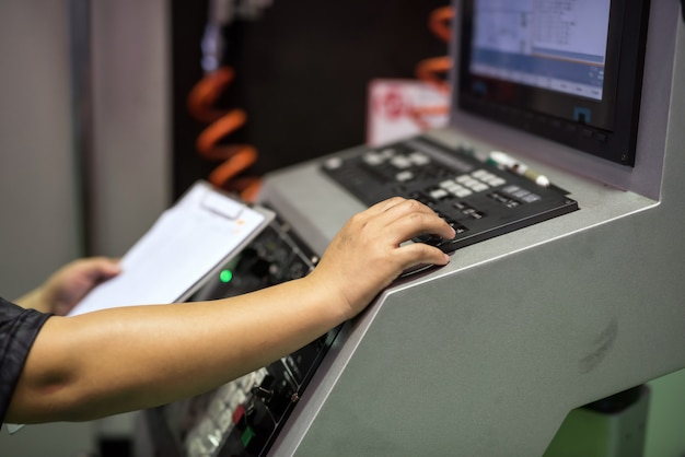 Operaio sulla tastiera per comandare la macchina