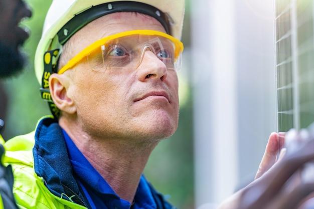 Uomo dell'ingegnere tecnico dell'operaio di fabbrica che mostra e che controlla il pannello della cella solare