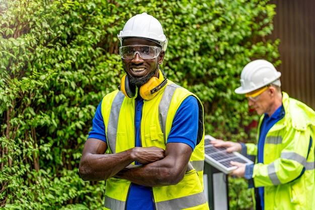Fiducia in piedi dell'uomo dell'ingegnere tecnico dell'operaio di fabbrica con l'abito da lavoro verde e il casco di sicurezza di fronte al lavoratore che controlla il pannello delle celle solari