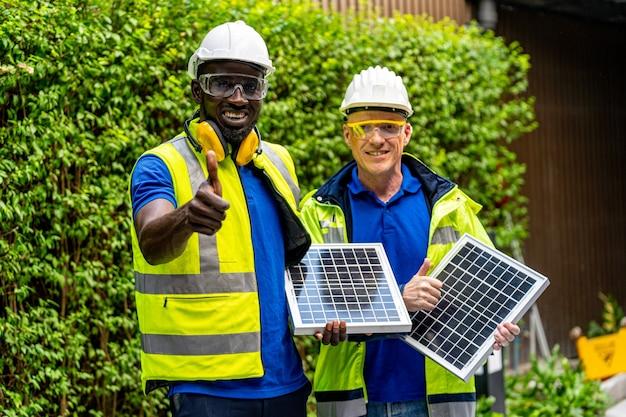 Uomini di ingegnere tecnico operaio di fabbrica che mostrano e controllano il pannello a celle solari per la tecnologia sostenibile con suite di lavoro verde