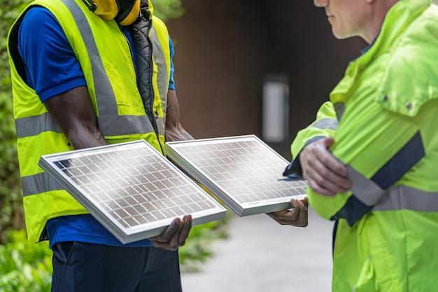 Uomini dell'ingegnere tecnico dell'operaio di fabbrica che mostrano e controllano il pannello delle celle solari per la tecnologia sostenibile.