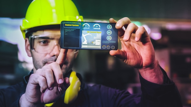 L'operaio di fabbrica utilizza il futuro dispositivo con schermo olografico per controllare la produzione