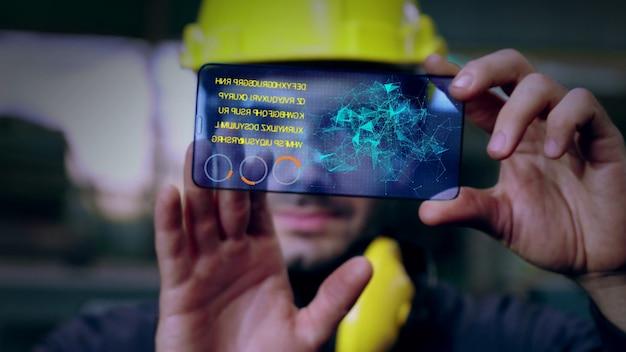 Il lavoratore di fabbrica utilizza il futuro dispositivo con schermo olografico per controllare la produzione