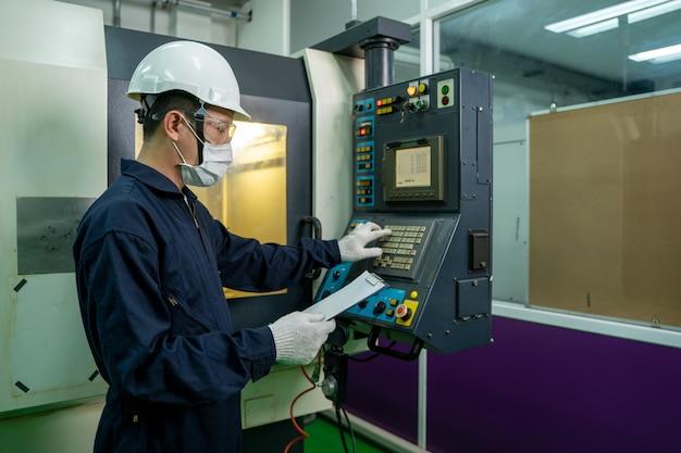 Operaio di fabbrica che indossa la maschera protettiva lavorando e controllando la macchina in una grande fabbrica industriale.