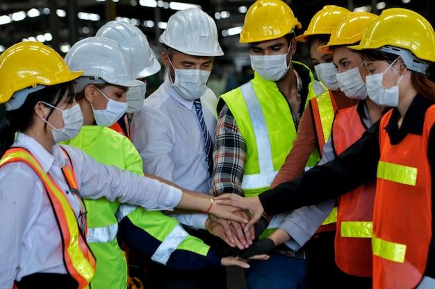 Gli operai di fabbrica costruiscono il morale e combattono durante l'epidemia di covid-19, concetto di settore