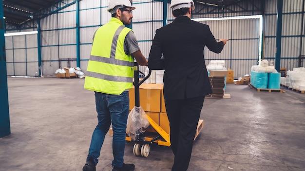 Gli operai consegnano il pacchetto di scatole su un carrello di spinta nel magazzino.