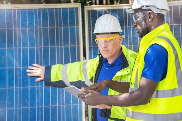 Operai di fabbrica che mostrano e controllano il pannello delle celle solari per la tecnologia sostenibile