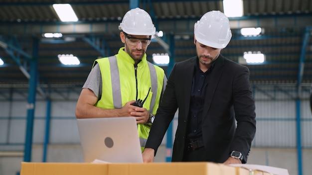 Operai che lavorano e discutono del piano di produzione in fabbrica