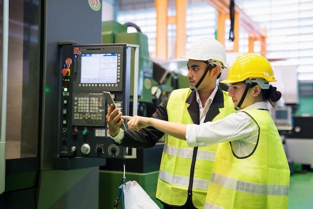Gli ispettori di fabbrica con elmetto protettivo controllano l'app aziendale nel tablet digitale sulla fresatrice per torni cnc