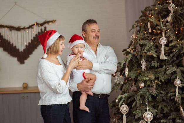 Nonni e nipote felici in cappelli di babbo natale vicino all'albero di natale