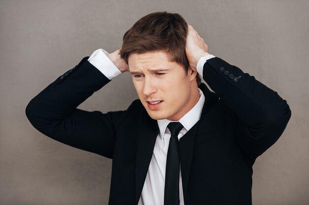 Di nuovo fallito. giovane frustrato in abiti da cerimonia che tocca la testa con le mani mentre si sta in piedi su uno sfondo grigio