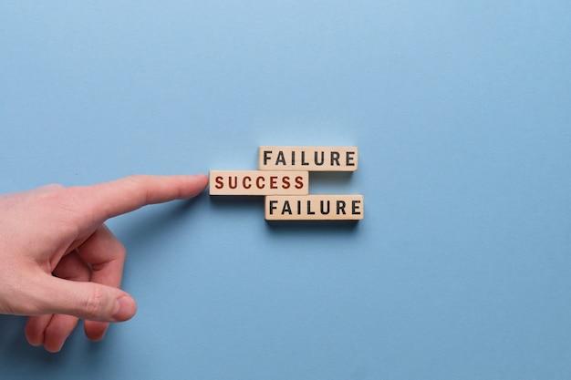 Concetto di successo e di guasto - la mano tiene il blocco di legno con l'iscrizione su uno spazio blu.