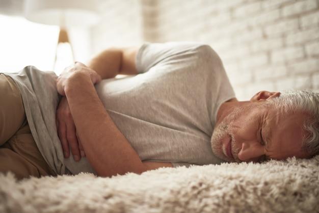 Svenimento dell'uomo anziano a letto dolore allo stomaco dolore alla pancia.
