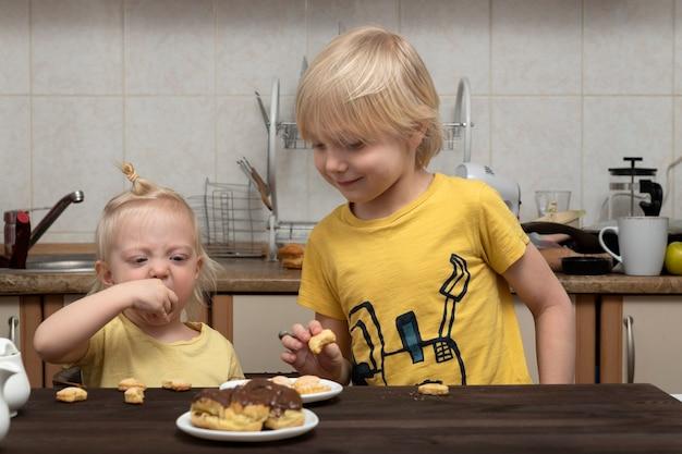 Fratello e sorella biondi stanno facendo colazione in cucina. famiglia amichevole.