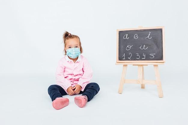 Ragazza bionda che indossa un grembiule rosa per bambini e una mascherina chirurgica per proteggersi dal covid-19 in classe