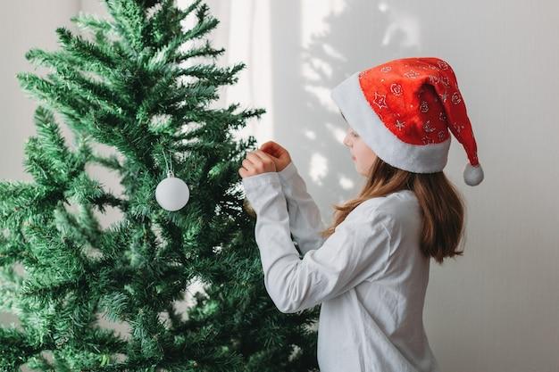 Una scolaretta bionda decora un albero di natale artificiale con un cappello da babbo natale con decorazioni natalizie. capodanno, celebrazione della cucina tradizionale.