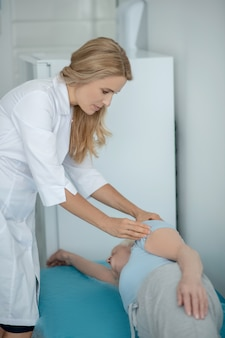Biondo giovane medico esaminando un paziente anziano