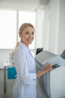 Biondo giovane medico in piedi in ufficio e sorridente