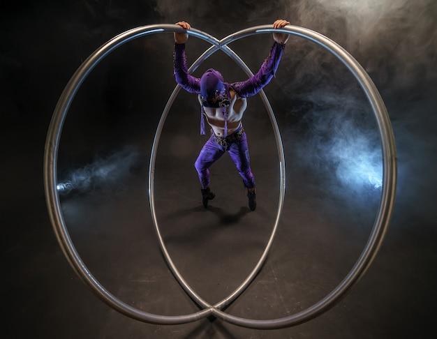 Personaggio fiabesco assassino in un mantello viola con un cappuccio con due grandi cerchi a ruota cyr
