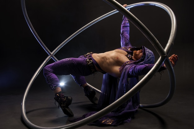 Assassino personaggio fiabesco in un mantello viola con cappuccio con due grandi ruote cyr in posizione di danza
