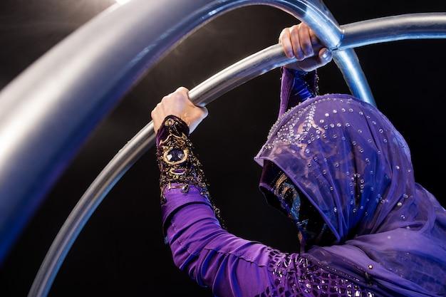 Personaggio fiabesco assassino in un mantello viola con un cappuccio con due grandi cerchi di metallo.