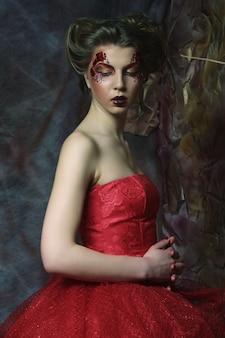 Fiaba. teatro. donna in abito rosso. acconciatura e trucco fantastici. fantasia.